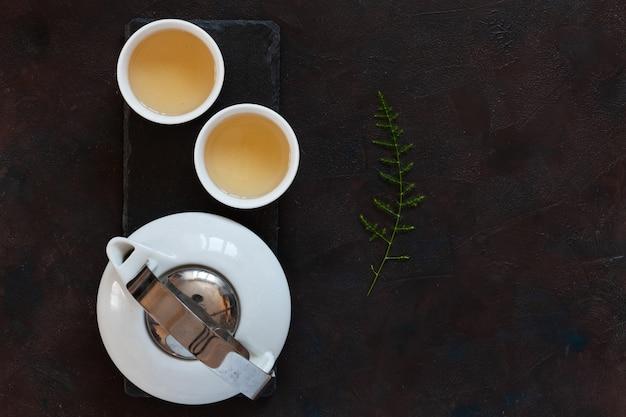 Porcelana branca conjunto de chá asiático com chá verde leite oolong na mesa de pedra negra Foto Premium