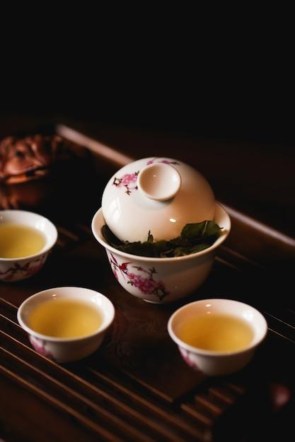 Porcelana gaiwan, três xícaras de chá chinês e dourado sapo na mesa de chá. Foto gratuita