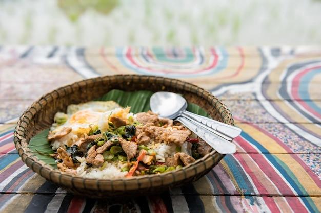Porco e ovo de manjericão tailandês perto do campo de arroz Foto Premium