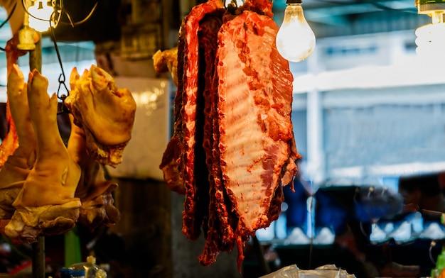 Porco pendurado no gabinete para venda no mercado local, tailândia Foto Premium