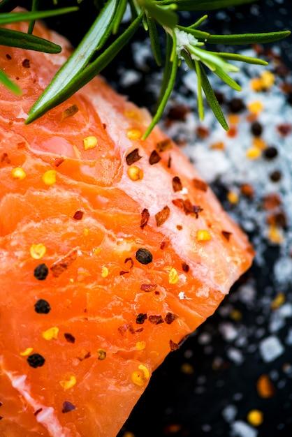 Porções de filés de salmão cru fresco com ervas aromáticas e azeite Foto Premium