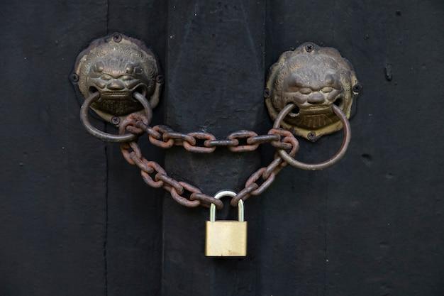 Porta antiga com aldrava de cabeça de leão é trancada por uma corrente velha e um cadeado. Foto Premium