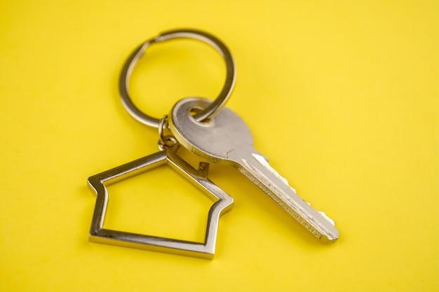 Porta-chaves de metal em forma de casa com uma chave amarela. Foto Premium