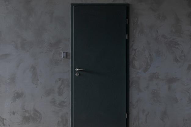 Porta de metal com sinalização na parede de concreto cinza Foto Premium