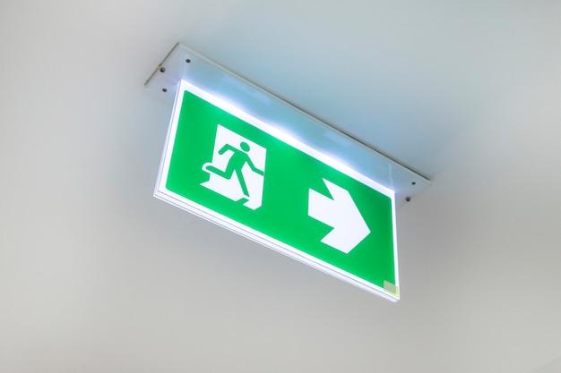 Porta de saída da porta de saída de emergência do fogo no teto. sinal verde da saída de emergência que mostra a maneira. Foto Premium