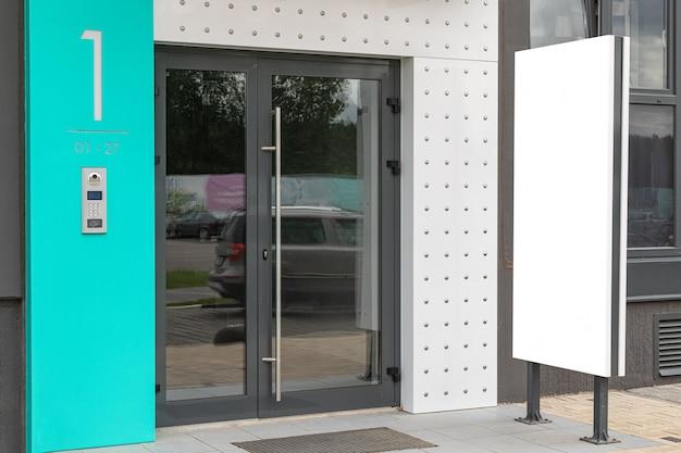 Porta de vidro de acesso ao prédio com banner de propaganda em branco perto dele Foto Premium