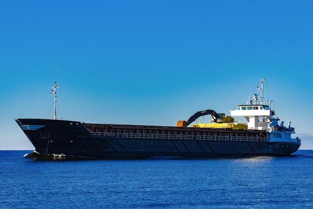 Porta-granel à vela preta. navio de carga com escavadeira de longo alcance movendo-se em águas paradas em dia de sol à beira-mar Foto Premium