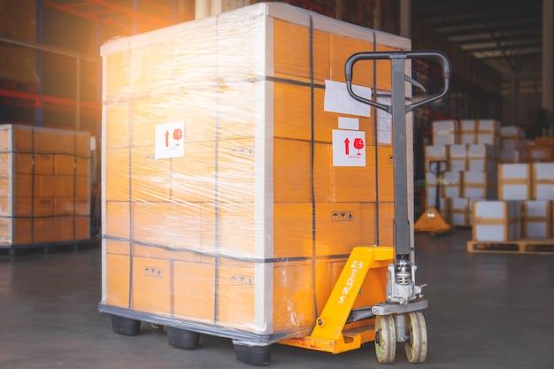 Porta paletes manuais com transporte de paletes de mercadorias para transporte Foto Premium