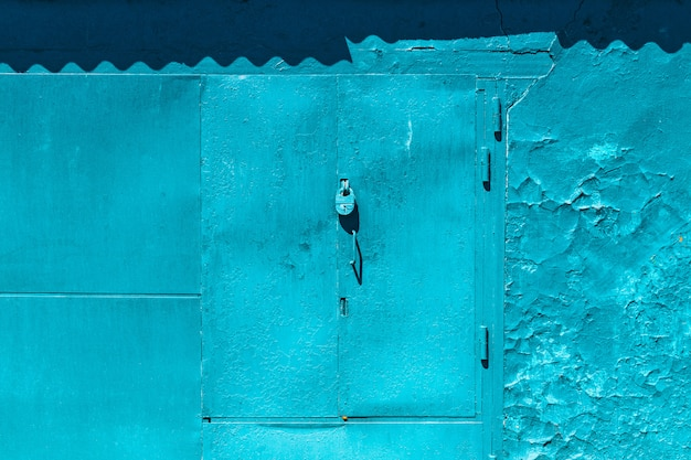 Portão de garagem azul imperfeito fechado com close-up de cadeado Foto Premium