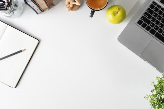 Portátil da mesa de escritório, papel do caderno, lápis, livro e café no espaço de trabalho branco da tabela. Foto Premium
