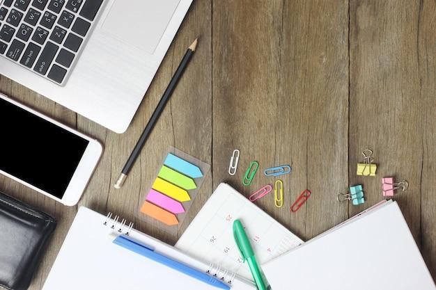 Portátil da vista superior, smartphone, carteira, pena, lápis, e calendário colocado em um de madeira marrom. Foto Premium