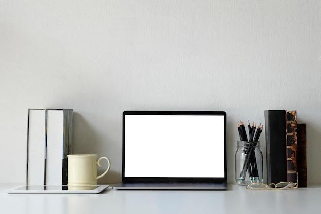 Portátil do modelo do espaço de trabalho do escritório, livros, lápis e caneca de café na mesa de escritório. Foto Premium