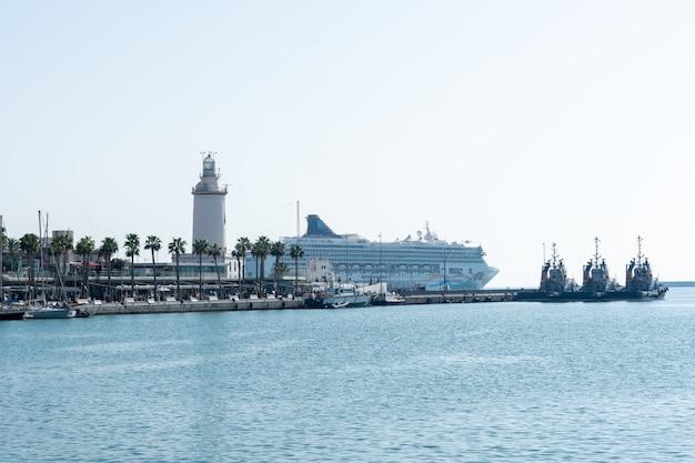 Porto de málaga com o cruzeiro de farol e passageiros em segundo plano Foto Premium