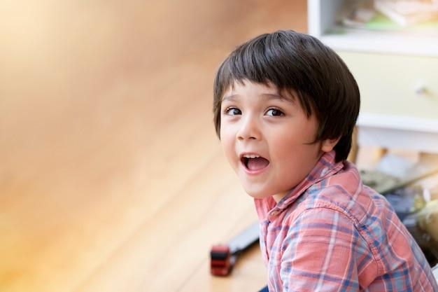 Portraot criança sentada no chão de madeira, relaxando em casa, foco suave de garoto garoto olhando com rosto sorridente enquanto brincava sozinho na sala de jogos. conceito de crianças positivas. Foto Premium