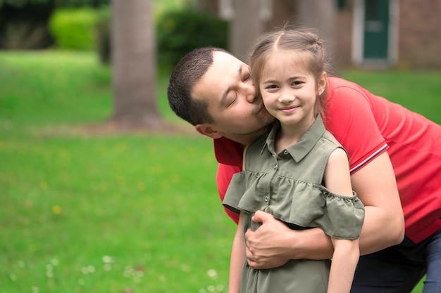 Portret do pai que beija a filha na bochecha para fora no fundo da porta. homem coreano beijando sua filha. Foto Premium