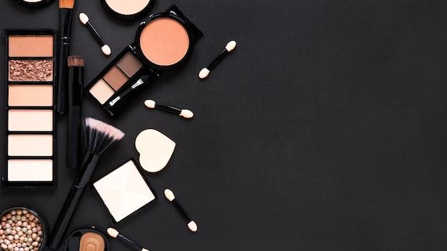 Pós faciais com escovas em pó na mesa escura Foto Premium