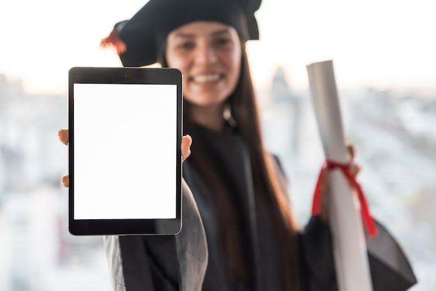 Pós-graduação segurando tablet mock-up Foto gratuita