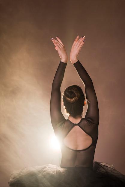 Pose de bailarina vista traseira com fumaça Foto gratuita