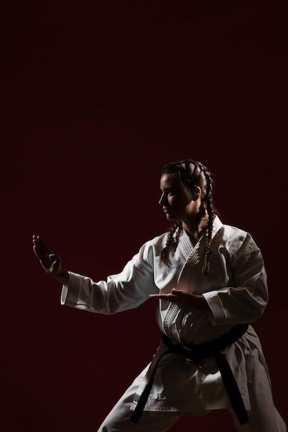 Posição de luta da mulher em uniforme branco de karatê Foto gratuita