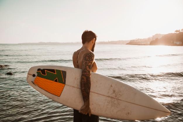 Posição homem, com, surfboard, ligado, praia Foto gratuita