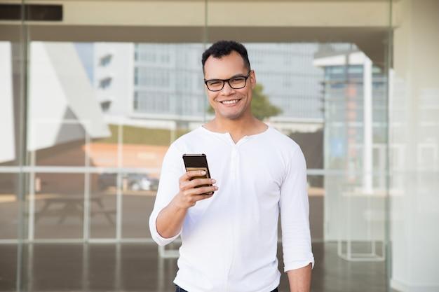 Posição homem, em, edifício escritório, segurando telefone, em, mão, sorrindo Foto gratuita