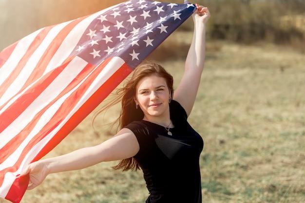 Posição mulher, em, campo, e, bandeira americana segurando Foto gratuita