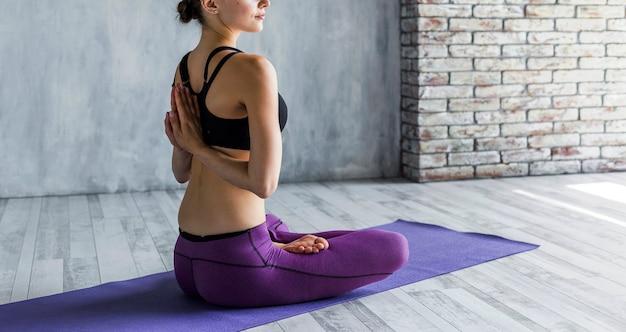Posição mulher, em, loto, ioga posa, com, mãos costas dela Foto gratuita