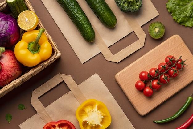 Posição plana da cesta de vegetais orgânicos com sacola de compras Foto gratuita