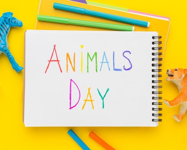 Posição plana de estatuetas de animais e escrita multicolorida no caderno para o dia dos animais Foto gratuita