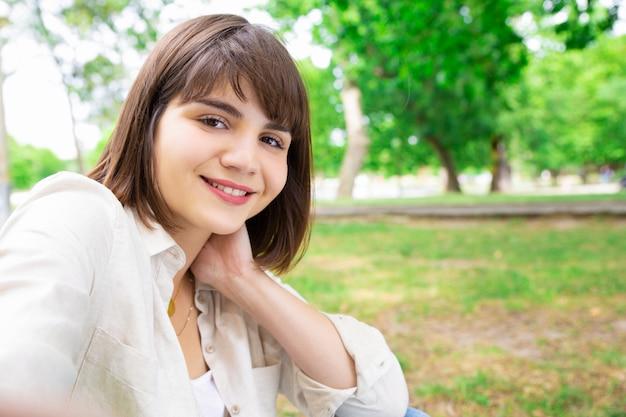 Positiva mulher bonita tirando foto de selfie e sentado no gramado Foto gratuita