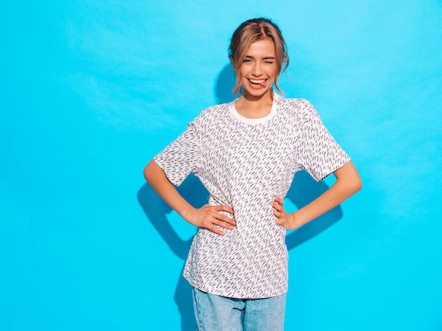 Positivo feminino sorrindo. engraçado modelo posando perto da parede azul no estúdio. mostra a língua e piscadelas Foto gratuita