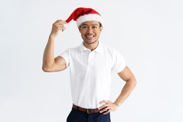 Positivo homem asiático tocando seu chapéu de papai noel Foto gratuita
