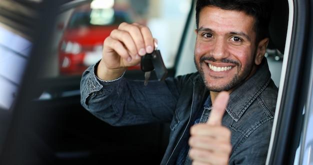 Positivo jovem segurando uma chave sentado em um carro com o polegar para cima Foto Premium