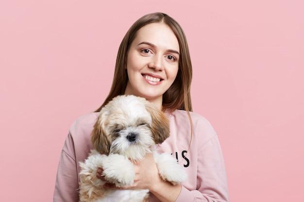 Positve fêmea com cabelos longos e expressão satisfeita mantém seu cachorrinho favorito, isolado sobre a parede rosa. mulher feliz com animal de estimação, tenha bons relacionamentos. conceito de pessoas e animais Foto Premium