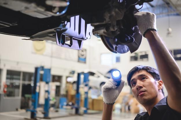 Posse mecânica masculina asiática e lanterna brilhante para examinar a pastilha de freio a disco do carro Foto Premium
