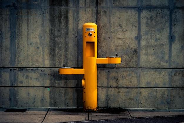 Post exterior de pedestal amarelo contra a parede Foto gratuita