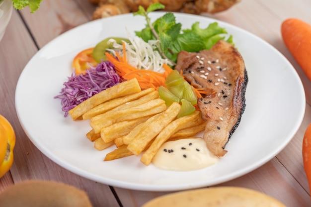 Posta de peixe com batatas fritas, kiwi, alface, cenoura, tomate e repolho em um prato branco. Foto gratuita