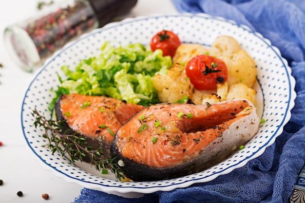 Posta de salmão assada com couve-flor, tomate e ervas. nutrição apropriada. Foto Premium