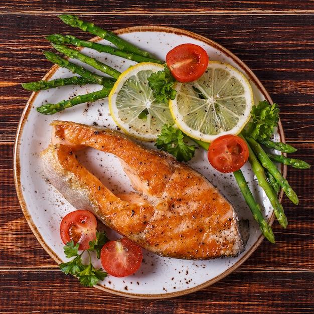 Posta de salmão grelhada servida com aspargos, tomate e limão. Foto Premium