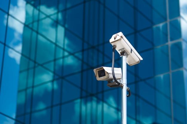 Poste com duas câmeras de videovigilância brancas no prédio de vidro do grande escritório Foto Premium