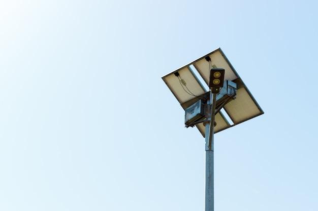 Poste de luz com painel de células solares no fundo do céu azul Foto Premium