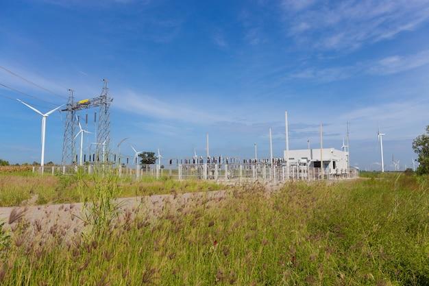 Postes de electricidade e usina ou estação com turbina de vento na natureza ao ar livre Foto Premium