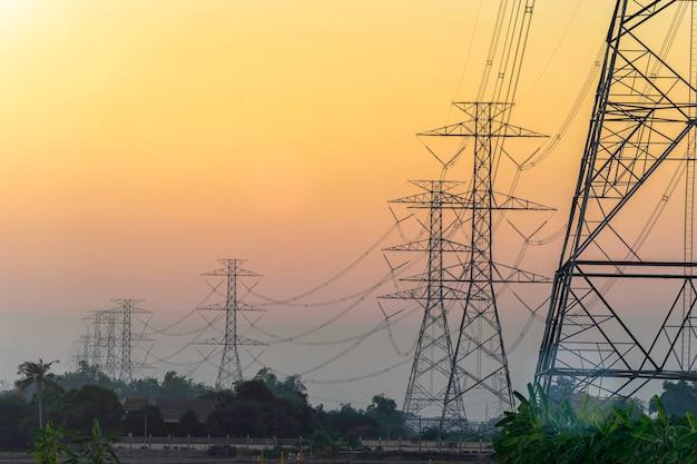Postes elétricos de alta tensão no céu pôr do sol Foto Premium