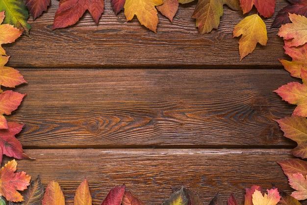 Postura plana com armação de borda de folhas de outono em fundo de madeira escuro rústico. Foto Premium