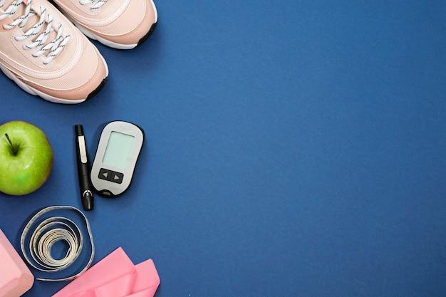 Postura plana com conceito de perda de peso dieta diabetes. tênis, fita métrica, glicosímetro em um azul Foto Premium