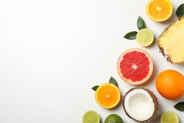 Postura plana com frutas exóticas em fundo branco, espaço para texto Foto Premium