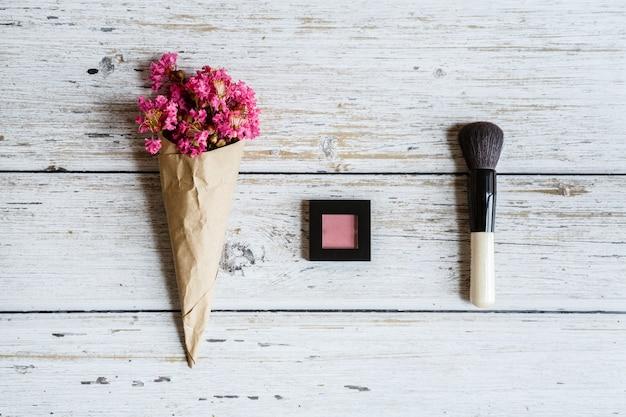 Postura plana com maquiagem blush, pincel e flores na mesa de madeira Foto Premium