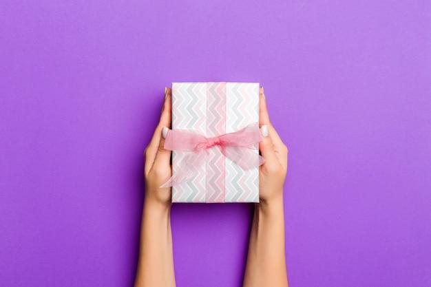 Postura plana das mãos de mulher segurando presente embrulhado e decorado com laço roxo. Foto Premium