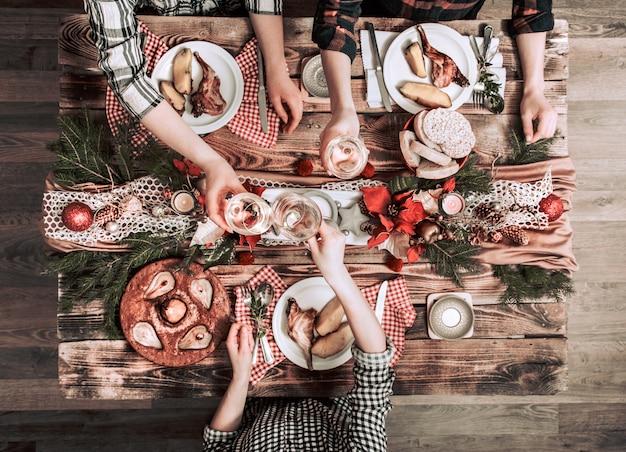 Postura plana de amigos mãos comendo e bebendo juntos. vista superior das pessoas, festa, reunião, comemorando juntos na mesa rústica de madeira Foto gratuita