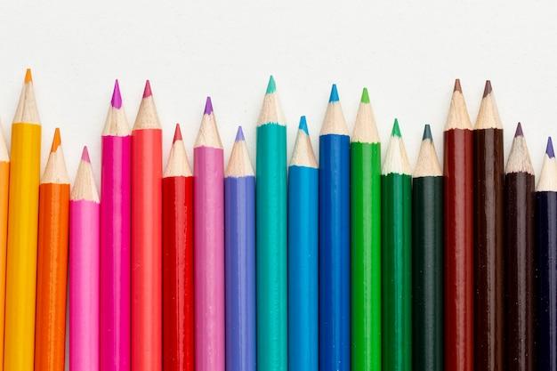 Postura plana de arranjo de lápis coloridos Foto gratuita